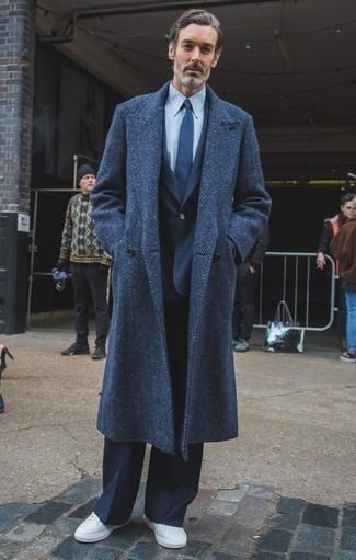 Moda para hombres de 40 años: Elige un abrigo largo de espiguilla azul marino y un traje azul marino para un perfil clásico y refinado. Tenis de cuero blancos añadirán un nuevo toque a un estilo que de lo contrario es clásico.