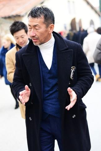 Cómo combinar un traje azul marino en clima fresco: Haz de un traje azul marino y un abrigo largo azul marino tu atuendo para una apariencia clásica y elegante.