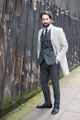 Cómo combinar: abrigo largo gris, traje de tres piezas en gris oscuro, camisa de vestir blanca, zapatos oxford de cuero negros