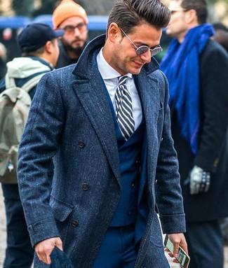 Cómo combinar: abrigo largo azul marino, traje de tres piezas azul marino, camisa de vestir blanca, corbata de rayas verticales en azul marino y blanco