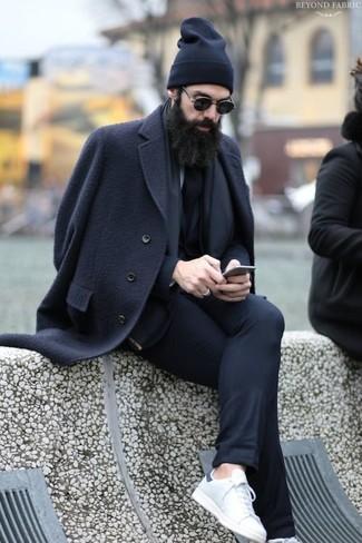 Cómo combinar: abrigo largo negro, traje negro, tenis de cuero blancos, gorro negro