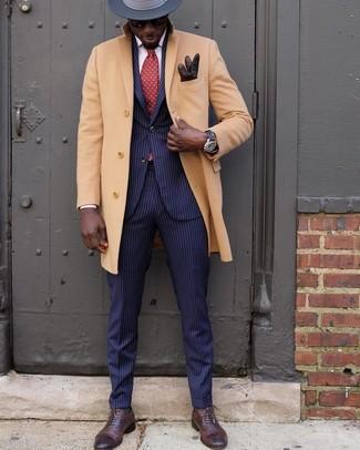 Cómo combinar: abrigo largo marrón claro, traje de rayas verticales azul marino, zapatos oxford de cuero en marrón oscuro, sombrero de lana en gris oscuro