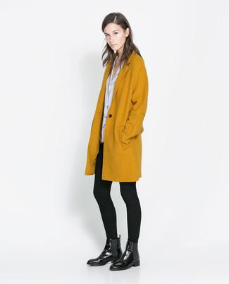 Cómo combinar: abrigo mostaza, blusa de manga corta estampada en blanco y negro, leggings negros, botines chelsea de cuero negros