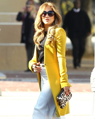 Look de Jennifer Lopez: Abrigo Mostaza, Blusa sin Mangas Negra, Pantalones Anchos Blancos, Cartera Sobre de Ante de Leopardo en Beige