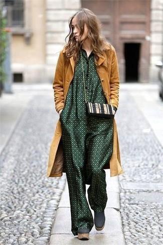 Cómo combinar: abrigo mostaza, mono a lunares verde oscuro, botines de ante gruesos verde oscuro, bolso bandolera de cuero en negro y blanco