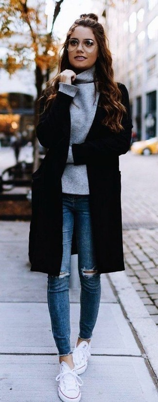 La versatilidad de un abrigo negro y unos vaqueros pitillo desgastados azules los hace prendas en las que vale la pena invertir. Tenis de lona blancos añaden un toque de personalidad al look.
