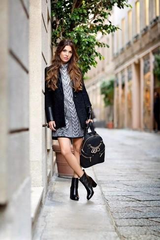 Cómo combinar: abrigo negro, vestido jersey plateado, botines de cuero negros, mochila de cuero negra