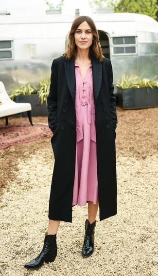 Cómo combinar: abrigo negro, vestido midi rosado, botas camperas de cuero negras
