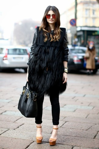 Cómo combinar: abrigo sin mangas de pelo negro, cazadora de aviador de cuero negra, vaqueros pitillo negros, sandalias de tacón de cuero gruesas marrón claro