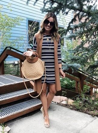 Cómo combinar: abrigo sin mangas marrón, vestido recto de rayas horizontales en negro y blanco, sandalias con cuña de cuero marrón claro, bolsa tote de paja marrón claro