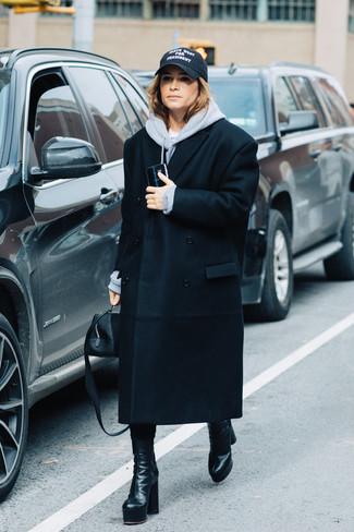 Cómo combinar: abrigo negro, sudadera con capucha gris, botas a media pierna de cuero negras, cartera de cuero negra