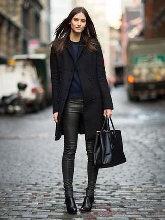 Cómo combinar: abrigo negro, sudadera azul marino, pantalones pitillo de cuero verde oscuro, botines de cuero negros
