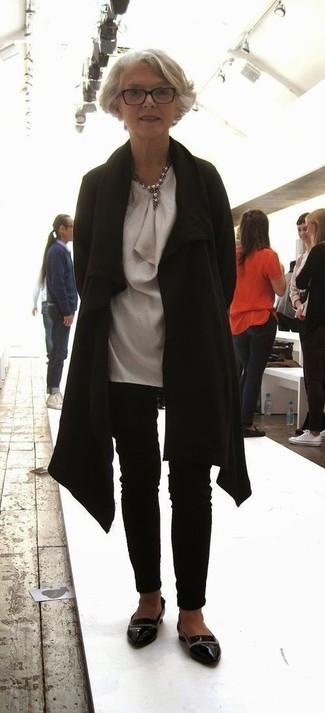 Moda para mujeres de 60 años: Equípate un abrigo negro junto a unos pantalones pitillo negros para lograr un look de vestir pero no muy formal. Mocasín de cuero negros son una opción perfecta para completar este atuendo.
