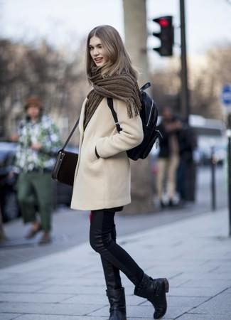 Cómo combinar: abrigo en beige, vaqueros pitillo de cuero negros, botas a media pierna de cuero negras, mochila de cuero negra