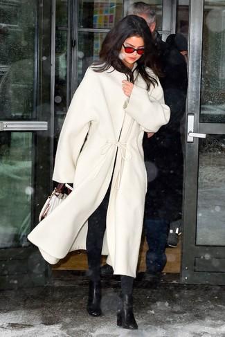 Cómo combinar: abrigo blanco, vaqueros pitillo negros, botines de cuero negros, bolso de hombre de cuero blanco