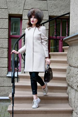 Cómo combinar: abrigo en beige, vaqueros pitillo de cuero negros, tenis de lona blancos, bolso de hombre de cuero en marrón oscuro