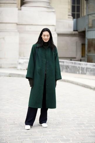 Cómo combinar: abrigo verde oscuro, jersey de cuello alto en gris oscuro, pantalones anchos negros, tenis de cuero blancos