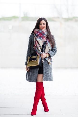 La versatilidad de un abrigo gris oscuro y un vestido ajustado negro los hace prendas en las que vale la pena invertir. Botas sobre la rodilla de ante rojas son una opción estupenda para completar este atuendo.