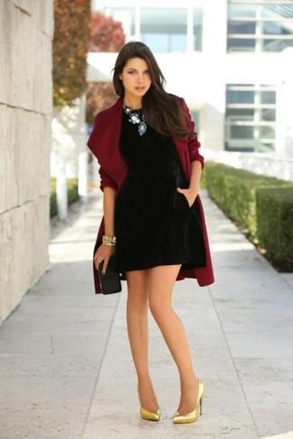 Cómo combinar: abrigo burdeos, vestido recto de terciopelo negro, zapatos de tacón de cuero dorados, cartera sobre de cuero negra
