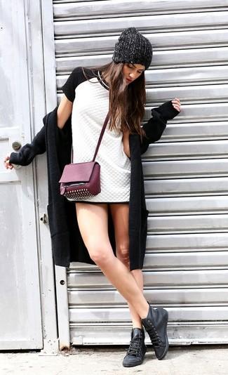 Cómo combinar: abrigo negro, vestido tubo acolchado en blanco y negro, zapatillas altas de cuero negras, bolso bandolera de cuero con tachuelas morado