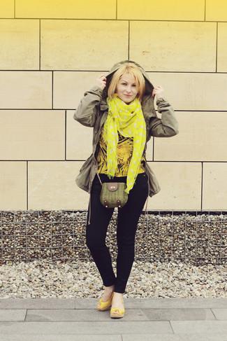 Cómo combinar: anorak verde oliva, blusa de manga larga amarilla, vaqueros pitillo azul marino, sandalias con cuña de cuero amarillas