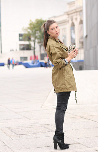 Cómo combinar: anorak verde oliva, jersey con cuello circular de leopardo en blanco y negro, vaqueros pitillo en gris oscuro, botines de cuero negros