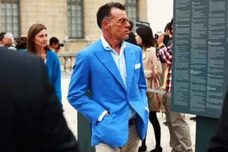Cómo combinar una camisa de manga larga azul: Empareja una camisa de manga larga azul con un pantalón chino marrón claro para conseguir una apariencia relajada pero elegante.