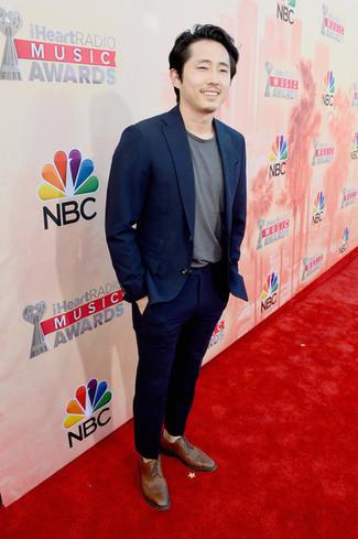 Cómo combinar: blazer azul marino, camiseta con cuello circular gris, pantalón chino azul marino, zapatos brogue de cuero marrónes