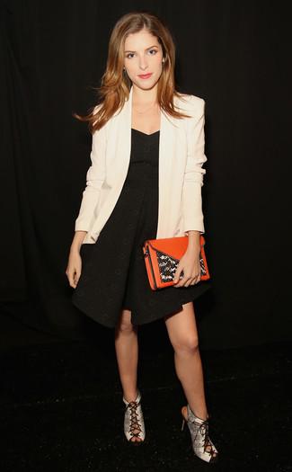 Cómo combinar: blazer blanco, vestido de vuelo negro, sandalias de tacón de cuero con print de serpiente grises, cartera sobre de cuero naranja