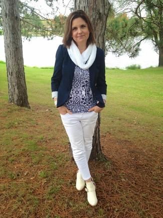 Cómo combinar: blazer azul marino, blusa sin mangas estampada en azul marino y blanco, vaqueros blancos, botines de cuero en beige