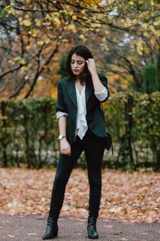 Cómo combinar: blazer de rayas verticales negro, blusa sin mangas con volante blanca, vaqueros pitillo negros, botines de cuero negros