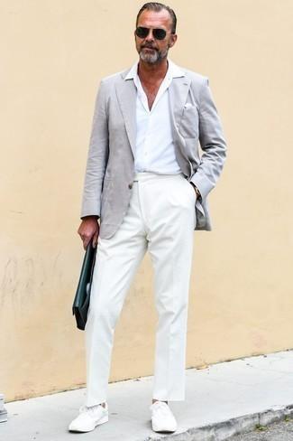 Cómo combinar un blazer gris: Casa un blazer gris con un pantalón de vestir blanco para rebosar clase y sofisticación. Si no quieres vestir totalmente formal, elige un par de tenis blancos.
