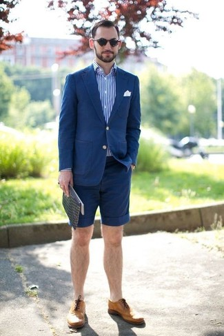 Cómo combinar: blazer de algodón azul, camisa de manga larga de rayas verticales en blanco y azul, pantalones cortos azul marino, zapatos brogue de cuero marrón claro