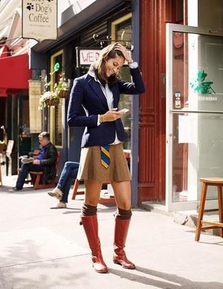 Un blazer azul marino y una minifalda tabaco son el combo perfecto para llamar la atención por una buena razón. Este atuendo se complementa perfectamente con botas de caña alta de cuero rojas.