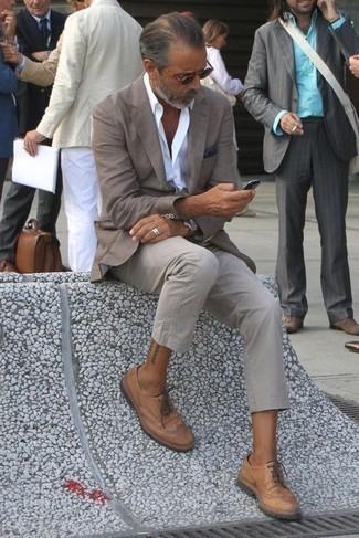 Cómo combinar unos zapatos brogue de cuero marrón claro: Si buscas un look en tendencia pero clásico, elige un blazer gris y un pantalón chino gris. ¿Te sientes valiente? Opta por un par de zapatos brogue de cuero marrón claro.