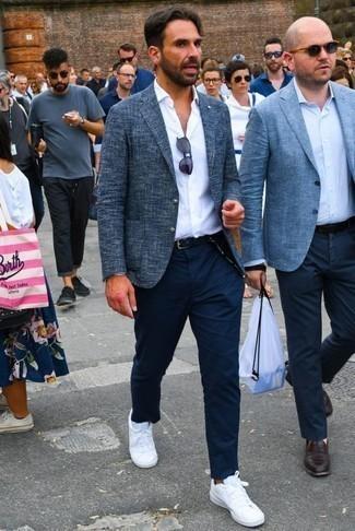 Una camisa de vestir de vestir con un pantalón chino azul marino: Si buscas un look en tendencia pero clásico, elige una camisa de vestir y un pantalón chino azul marino. ¿Quieres elegir un zapato informal? Opta por un par de tenis de lona blancos para el día.