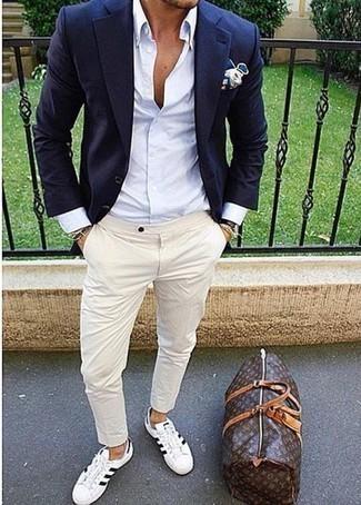Cómo combinar una bolsa de viaje de cuero en marrón oscuro: Ponte un blazer azul marino y una bolsa de viaje de cuero en marrón oscuro transmitirán una vibra libre y relajada. Opta por un par de tenis de lona en blanco y negro para mostrar tu inteligencia sartorial.