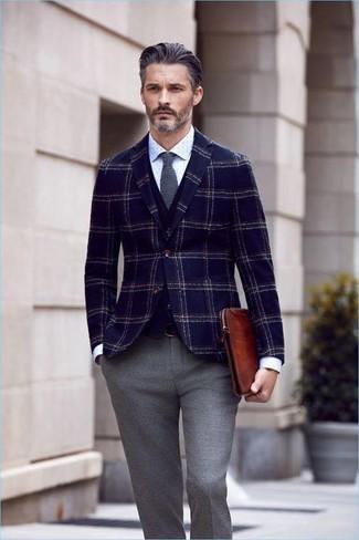 Cómo combinar una camisa de vestir a lunares en blanco y negro: Elige una camisa de vestir a lunares en blanco y negro y un pantalón de vestir de lana gris para un perfil clásico y refinado.