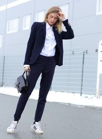 Cómo combinar: blazer azul marino, camisa de vestir blanca, pantalón de vestir azul marino, tenis de rayas horizontales en blanco y negro