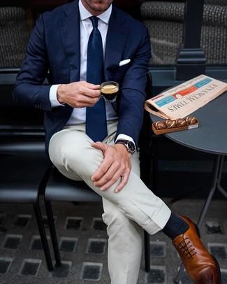 Cómo combinar: blazer azul marino, camisa de vestir blanca, pantalón de vestir en beige, zapatos oxford de cuero marrónes