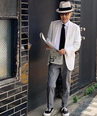 Cómo combinar: blazer blanco, camisa de vestir blanca, pantalón de vestir gris, tenis de lona en negro y blanco
