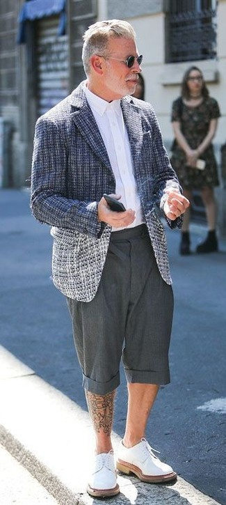 Cómo combinar: blazer de tweed azul marino, camisa de vestir blanca, pantalones cortos en gris oscuro, zapatos derby de cuero blancos