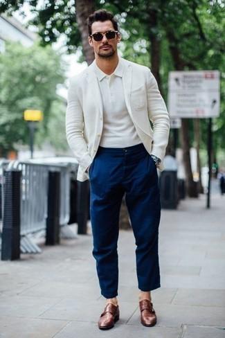 Cómo combinar una camisa polo blanca: Para un atuendo que esté lleno de caracter y personalidad usa una camisa polo blanca y un pantalón chino azul marino. Con el calzado, sé más clásico y complementa tu atuendo con zapatos con doble hebilla de cuero marrónes.