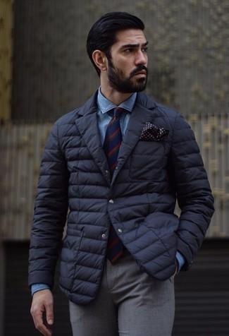 Cómo combinar: blazer acolchado negro, camisa vaquera azul, pantalón de vestir de lana gris, corbata de rayas verticales en rojo y azul marino