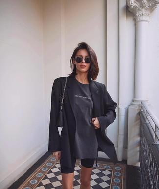 Cómo combinar: blazer negro, camiseta con cuello circular estampada en gris oscuro, mallas ciclistas negras, cartera de cuero negra