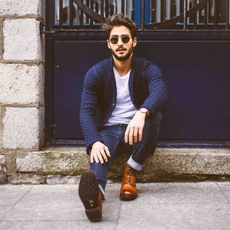 Cómo combinar: blazer de punto azul marino, camiseta con cuello circular blanca, vaqueros pitillo azul marino, botas formales de cuero marrónes