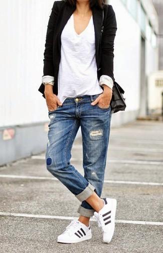 Un blazer negro y unos vaqueros boyfriend desgastados azules son el combo perfecto para llamar la atención por una buena razón. ¿Por qué no añadir deportivas blancas a la combinación para dar una sensación más relajada?