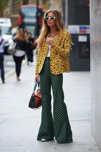 Cómo combinar: blazer con print de flores amarillo, camiseta sin manga blanca, pantalón de campana con print de flores verde oscuro, zapatos de tacón de cuero blancos