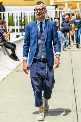 Cómo combinar una correa de lona tejida gris: Para un atuendo tan cómodo como tu sillón utiliza un blazer azul y una correa de lona tejida gris. Con el calzado, sé más clásico y haz tenis de cuero blancos tu calzado.