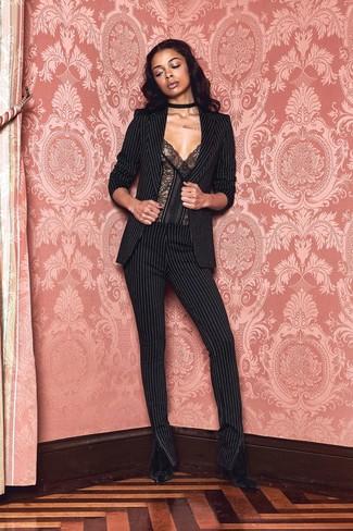 Cómo combinar: blazer de rayas verticales negro, corsé de encaje negro, pantalones pitillo de rayas verticales negros, botines de terciopelo negros